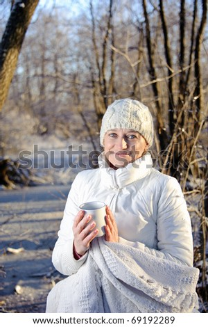 woman in white, with a mug in his hands, wrapped in a blanket in a winter forest.