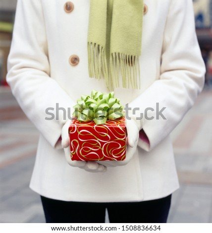 Woman in white wool coat holding Christmas gift present with festive wrapping paper and bow. Holiday gifts presents background.