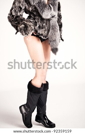woman in winter boots and fur, studio shot