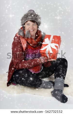 Woman in winter clothes with christmas present and white snowflakes