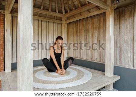 Woman in wooden  gazebo practicing yoga, stretching, touch her feets