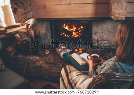 Woman in woollen socks by the fireplace. Unrecognisable relaxes by warm fire with a cup of hot drink and interesting book, warming up her feet. Cozy atmosphere. Winter and Christmas holidays concept. #768710299