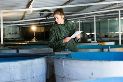 Woman in working clothes controlling fish growth in trout hatchery incubator