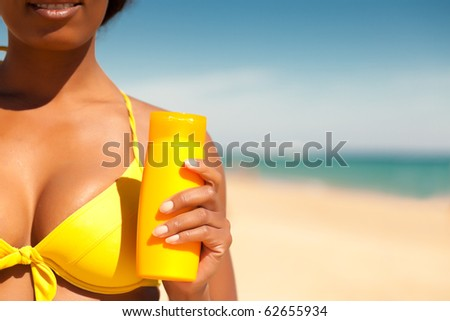 Woman in yellow bikini offering suncream on the beach in order to avoid sunburn, FOCUS is on hand, lots of copyspace