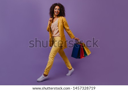 Woman in yellow costume posing after shopping. Adorable african girl holding store bags.