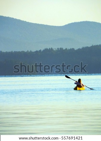 Woman in yellow kayak on calm morning lake paddling away from camera with foggy tree line and mountains in background - soft focus #557691421