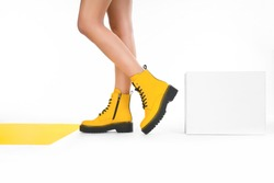woman in yellow leather shoes from the new collection on a white background girl's legs in fashionable eco-leather shoes fall-winter 2020. macro photo