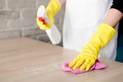 Woman in yellow rubber gloves cleaning table with pink cloth