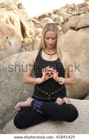 Woman in yoga pose Lotus with hand mudra outdoors. Elise Kost jewelry.