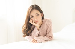Woman indoor portrait. Closeup of pensive young Asian woman in warm knitted pink clothes in the bedroom. Negative human facial expression.