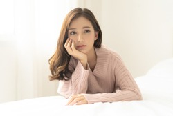 Woman indoor portrait. Young beautiful Asian woman in warm knitted pink clothes at home. fashion. Autumn, winter