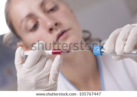 Woman injecting blood in test tube. Laboratory environment
