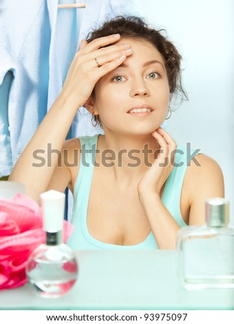 Woman inspecting skin for spots in the morning looking at the mirror