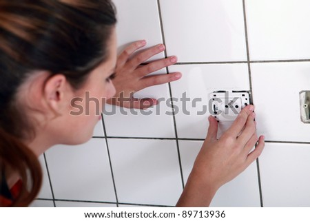 Woman installing electrical socket