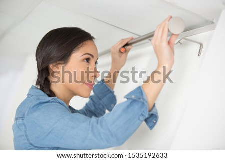 woman installing some new curtains at home #1535192633
