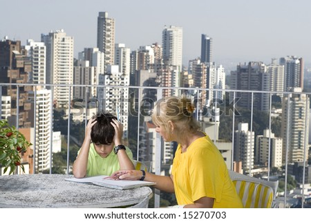 Woman instructing boy while sitting on balcony overlooking city. Horizontally framed photo. - stock photo