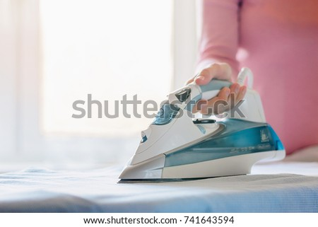 woman ironing a shirt with an electric iron on an ironing board on a light background #741643594