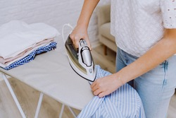 Woman ironing blue shirt with steam iron next to stack of washed and folded cotton shirts on ironing board after laundry. Housekeeping concept