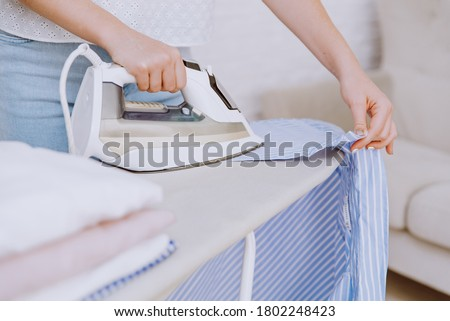 Woman ironing blue shirt with steam iron next to stack of washed and folded cotton shirts on ironing board after laundry. Housekeeping concept ストックフォト ©