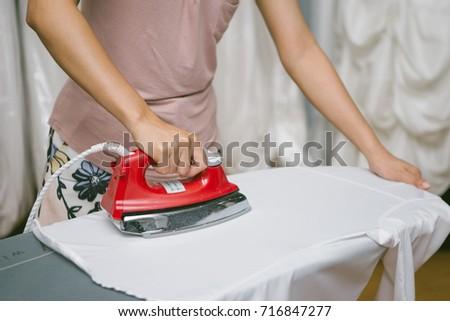 Woman ironing cloth on board #716847277