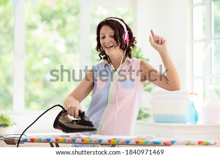 Woman ironing clothes, listening to music and dancing. Young female in headphones folding clothes at iron board. Dance and sing, home chores fun. Housewife cleaning house. Photo stock ©