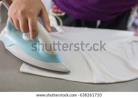 woman ironing clothes on ironing board #638261710