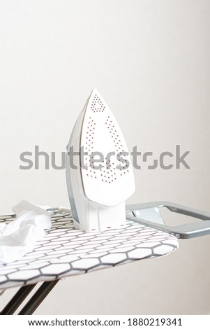 Woman ironing clothes with an iron on a board Photo stock ©