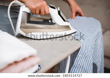 Woman ironing clothes with steam iron next to stack of clean cotton shirts on ironing board after laundry. Close up of household appliance Photo stock ©