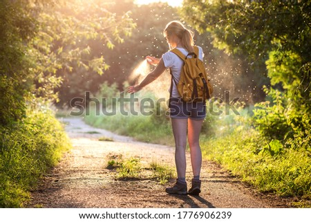 Woman is applying insect repellent against mosquito and tick on her hand during hike in nature. Skin protection against insect bite Photo stock ©