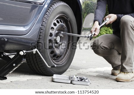 Woman is changing  tire with wheel wrench. - stock photo