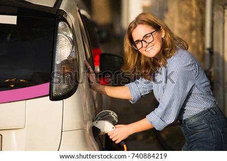 Woman is charging rental electric car