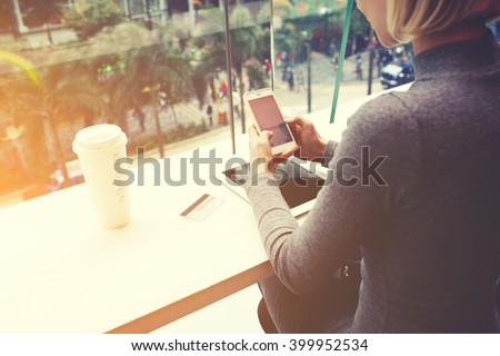 Woman is chatting on mobile phone, while is sitting in cafe at the table with digital tablet, credit card and take away coffee. Female is booking restaurant for dinner on-line via cell telephone #399952534