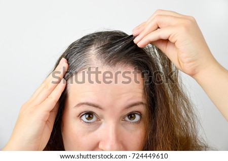 woman is checking white hair while looking at the mirror