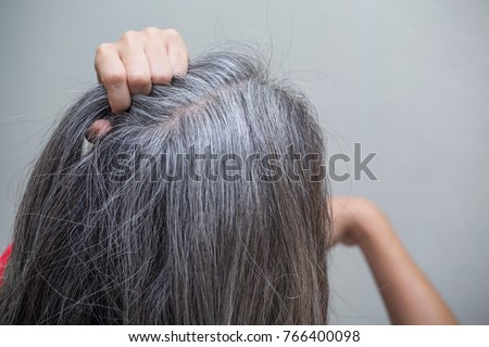 woman is checking white hair white looking at the mirror