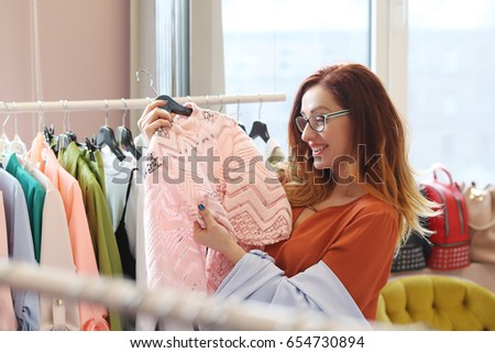 Shutterstock Woman is choosing a dress in clothing shop
