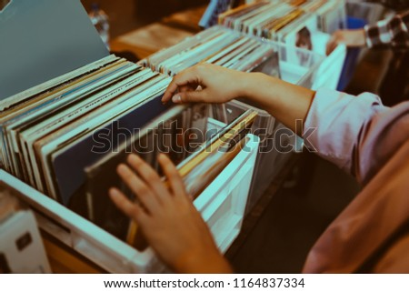 Woman is choosing a vinyl record in a musical store #1164837334