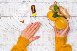 Woman is choosing natural healthy turmeric drink instead of traditional drugs and pills against flu. Alternative medicine concept. Top view, copy space