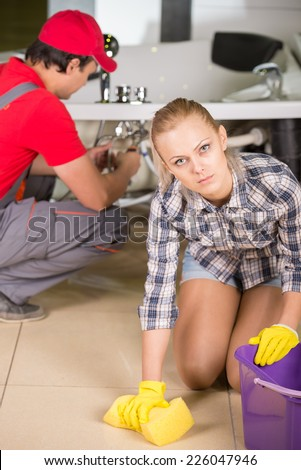 Woman is cleaning the floor in the bathroom, while plumber repairs the pipes.