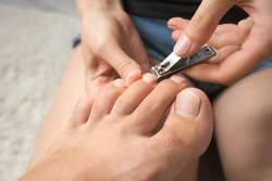 Woman is cutting man's nails on toes using nippers, closeup hands and feet view. She is sitting on floor on carpet at home and making pedicure. Hygiene and care for feet.