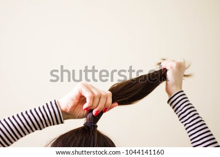 woman is doing her hair, straightened, combing, the disheveled bun on her head.  Dark hair is tied with a transparent spiral elastic band. Modern fast hairstyle. Cares about a beautiful hair. Copyspac