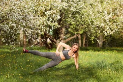 Woman is doing side plank outdoors in the blooming lawn in spring. Caucasian girl is planking, fitness instructor exercising outside.