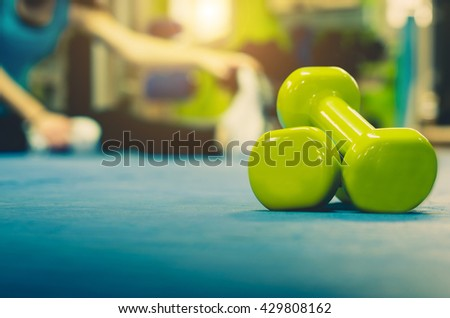 Woman is doing stretching at gym. Close up and focus on a pair of weights