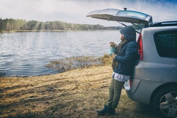 Woman is eating a hot dish from a thermos during a hike, leaning against a car by a lake, with a forest in the background