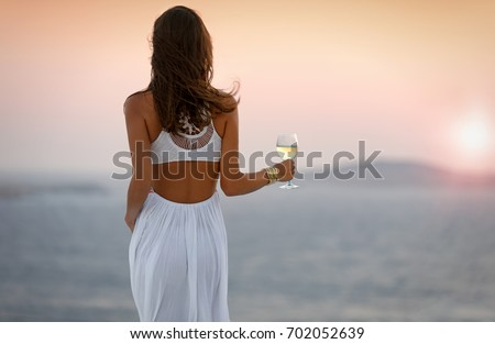 Woman is enjoying the sunset with a glass of wine