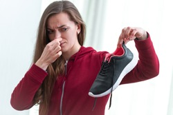 Woman is feeling unpleasant smell from sweaty running shoes after long sport training and active lifestyle. Footwear needs in cleaning and odor removal. Shoe care and shine