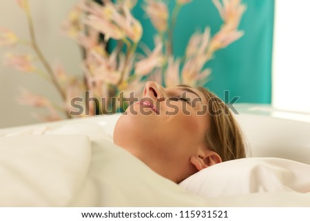 Woman is getting a soft pack in a Spa - she is doing wellness and seems to be very relaxed - stock photo