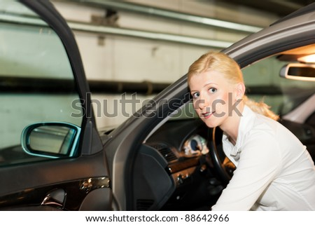 woman is getting into her car in the parking garage