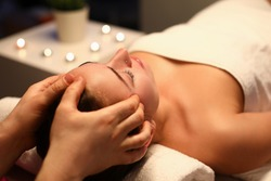 Woman is given rejuvenating facial massage in an aroma room. Relaxing facial massage techniques concept