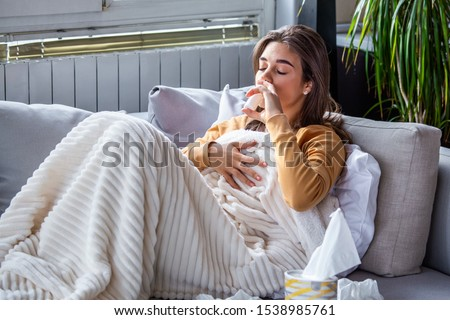 Woman is having flu and she is using nasal spray to help herself. Woman using nasal spray. Nasal spray to help a cold. Sick with a rhinitis woman dripping nose. Woman applies nasal spray #1538985761