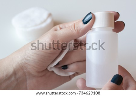 Woman is holding a nail polish remover. Girl hands on white table.